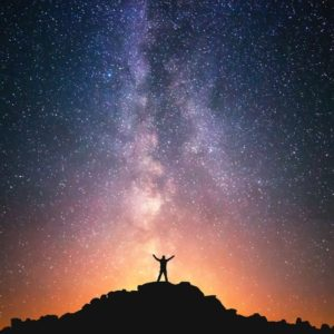 47194719 - man and the universe. a person is standing on the top of the hill next to the milky way galaxy with his hands raised to the air.